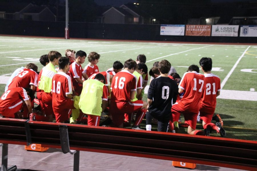 Coach Maner leads his team in prayer before the start of the game.