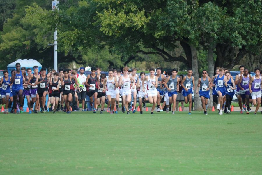 The varsity squad is breaking the line for the start of the race, trying to get out in front of the pack.