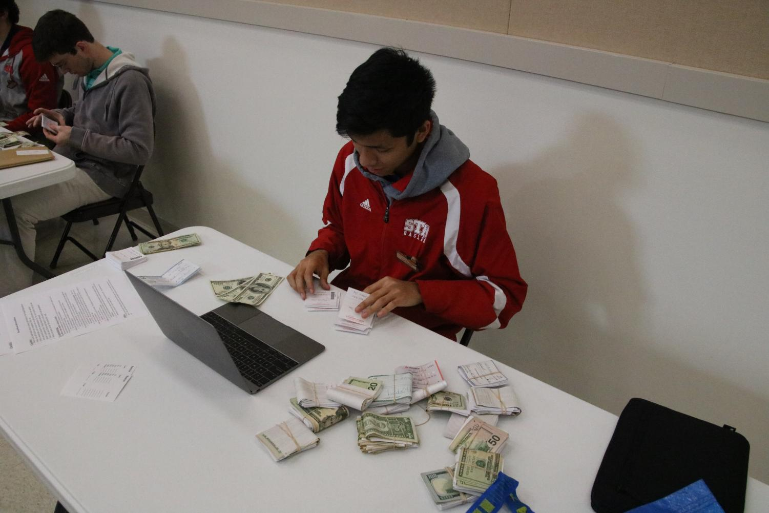 Round  Up board member Juan Vasquez '19 counts round up tickets and money after the turn in on February 14th. This was the final turn in to qualify for the 1st quota sellers holiday.